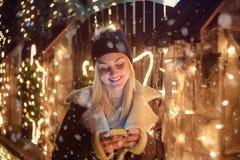 Портрет красивой девушки используя умный телефон перед домом d Стоковое Изображение RF