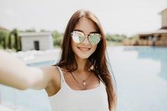 Портрет красивой девушки принимая selfie на бассейн девушки стола голубого мальчика смотрят заниматься серфингом моря сидя Стоковые Фото