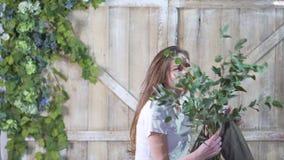 Портрет красивой девушки флориста с ветвью евкалипта против деревянного строба украшенного с цветками стоковое фото