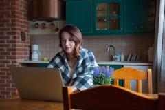 Портрет красивой девушки redhead в шотландке сидя на острословии таблицы Стоковое Изображение