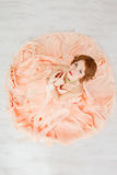 Портрет красивой девушки в бежевом платье персика Стоковое Изображение RF