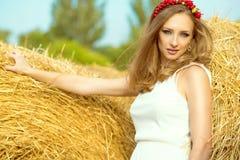 Портрет красивой девушки в белых sundress стоя среди стогов сена на сельской местности при гирлянда сделанная из искусственных пл Стоковое Изображение RF