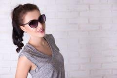 Портрет красивой девушки в солнечных очках над белой стеной Стоковые Фотографии RF