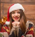 Портрет красивой девушки в шляпе Санты смотря камеру Стоковая Фотография