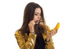 Портрет красивой девушки в яркой куртке с стеклами и с бананом в ее руке изолированной на белой предпосылке Стоковые Фотографии RF