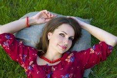 Портрет красивой девушки лежа на траве Стоковые Изображения RF
