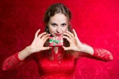 Портрет красивой девушки держа малый подарок на красном backgro Стоковые Изображения