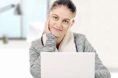 Портрет красивой девушки используя компьтер-книжку в офисе Стоковое Изображение RF