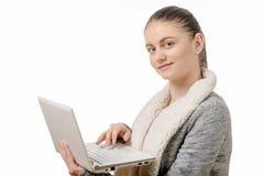 Портрет красивой девушки используя компьтер-книжку на белой предпосылке Стоковая Фотография