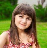 Портрет красивой девушки на предпосылке зеленой травы Стоковая Фотография