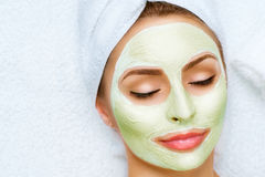 Портрет красивой девушки прикладывая лицевую маску стоковое фото