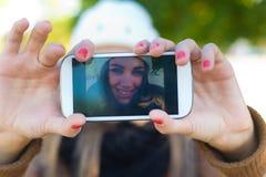 Портрет красивой девушки принимая selfie с мобильным телефоном Стоковые Изображения