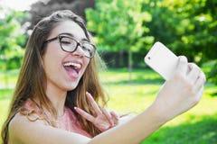 портрет красивой девушки принимая selfie с передвижным p Стоковое Фото