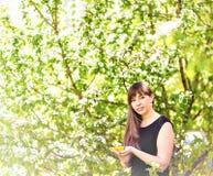 Портрет красивой девушки с букетом желтых одуванчиков внешних весной, фокус на глазах, предпосылка цветения яблока Стоковое Изображение RF