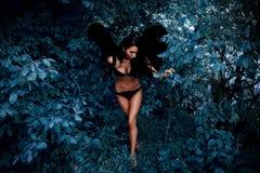 Портрет красивой девушки с чернотой подгоняет демона Стоковые Изображения