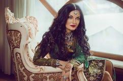Портрет красивой женщины в индийском платье традиционного китайския, при ее руки покрашенные с mehendi хны стоковая фотография