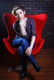 Портрет красивой женщины в красном кресле Стоковое Фото