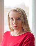 Портрет красивой женщины в красном платье в окне Стоковые Фотографии RF
