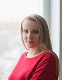 Портрет красивой женщины в красном платье в окне Стоковые Фото