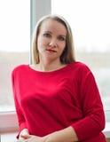Портрет красивой женщины в красном платье в окне Стоковое Изображение RF