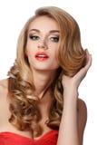 Портрет красивой женщины в красном платье делая вверх по ее волосам Стоковое фото RF