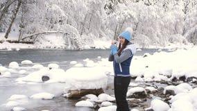 Портрет красивой женщины в лесе зимы около реки горы Женщина трет его руки и дышать теплые акции видеоматериалы