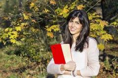 Портрет красивой женщины в парке осени, держа книгу Стоковая Фотография RF