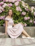 Портрет красивой женщины в розовом платье сидит на каменной лестнице на предпосылке цветков Стоковые Изображения