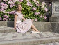 Портрет красивой женщины в розовом платье сидит на каменной лестнице на предпосылке цветков Стоковое фото RF