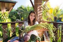 Портрет красивой женщины держа улыбку спаржи счастливую сидя на таблице на террасе лета с тропическим лесом Стоковое фото RF