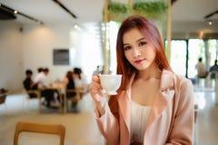Портрет красивой женщины держа чашку кофе в ее руке на кофейне предпосылки нерезкости Стоковые Изображения RF