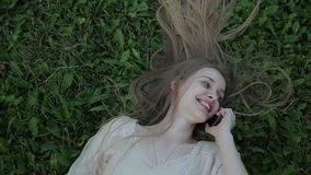 Портрет красивой женщины лежа на зеленой траве с телефоном видеоматериал