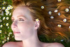 Портрет красивой женщины лежа на траве с цветками в волосах Стоковая Фотография