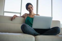 Портрет красивой женщины используя компьтер-книжку на софе на офисе Стоковое Изображение