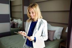 Портрет красивой женщины используя таблетку в спальне Стоковая Фотография RF
