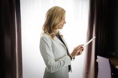 Портрет красивой женщины используя таблетку в спальне Стоковые Изображения