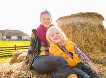 Портрет красивой женщины и милой девушки сидя на сене на ферме Стоковая Фотография