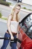 Портрет красивой женщины дозаправляя ее автомобиль Стоковые Изображения