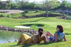 Портрет красивой женщины ослабляя во время играть гольф на зеленой предпосылке поля outdoors Тропический остров Бали Стоковая Фотография