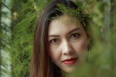 Портрет красивой женщины под смотреть листьев стоковое фото rf