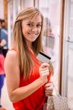 Портрет красивой женщины показывая ее кредитную карточку в магазине ювелира Стоковое Фото