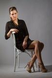 Портрет красивой женщины представляя в студии на chear Стоковые Фотографии RF