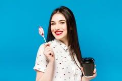 Портрет красивой женщины при lolly изолированный на голубой предпосылке Портрет красивой девушки брюнет с красным цветом Стоковое фото RF