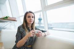 Портрет красивой женщины сидя на кресле в красивом современном кафе и нагревая с горячим питьем Стоковая Фотография