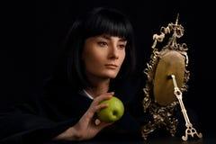 Портрет красивой женщины смотря в старом зеркале стоковое изображение