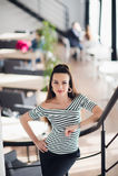 Портрет красивой женщины смотря камеру около большого окна Взрослое предприниматель кафа с приветствующей улыбкой в современном Стоковые Изображения