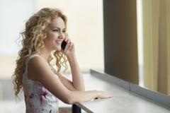 Портрет красивой женщины с испуская лучи улыбкой говоря на телефоне в кафе Стоковая Фотография