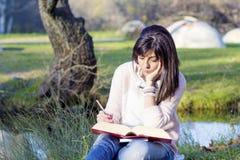 Портрет красивой женщины с книгой в парке осени Стоковая Фотография