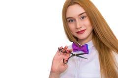 Портрет красивой женщины с роскошными волосами на белой предпосылке Она имеет ножницы в ее руках Ее профессия a Стоковые Изображения RF