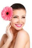 Портрет красивой женщины с яркой составляет держать розовую маргаритку в руках стоковые изображения